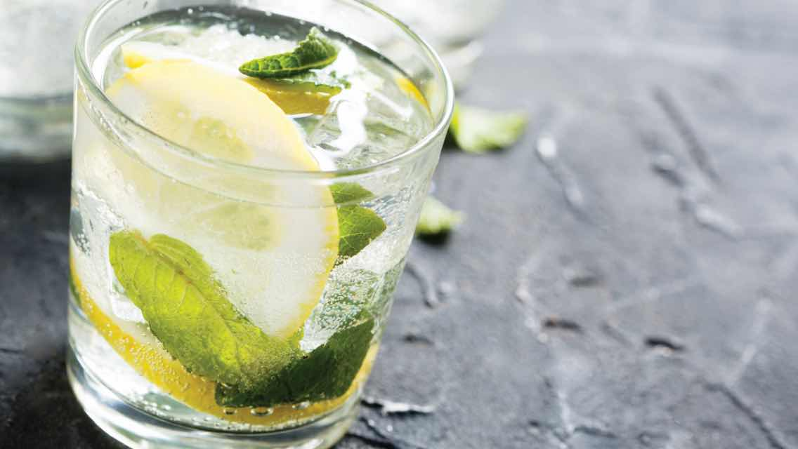 Clear drink with lemon and herbs in it on a black table.
