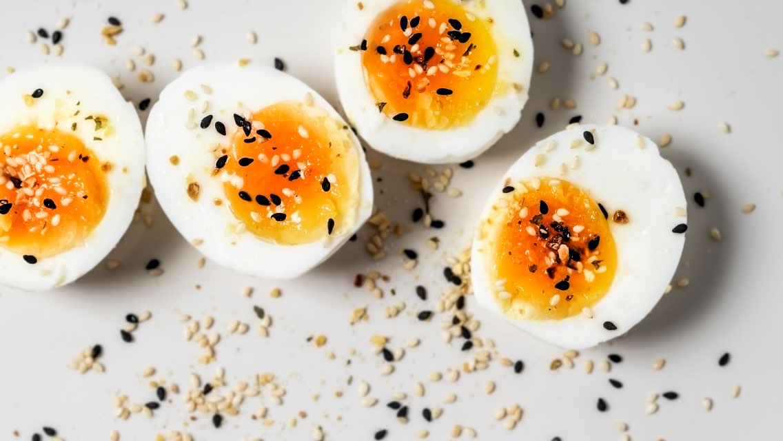Four halves of hard-boiled eggs with seasoning sprinkled on the top of them.