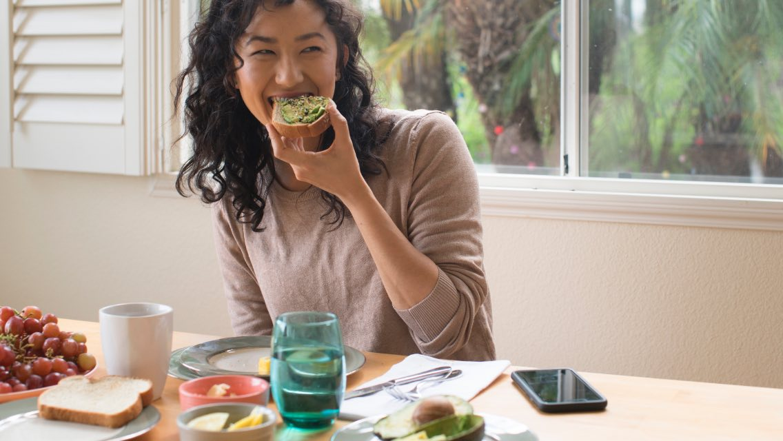 A woman smiling while eating avocado toast in the kitchen.