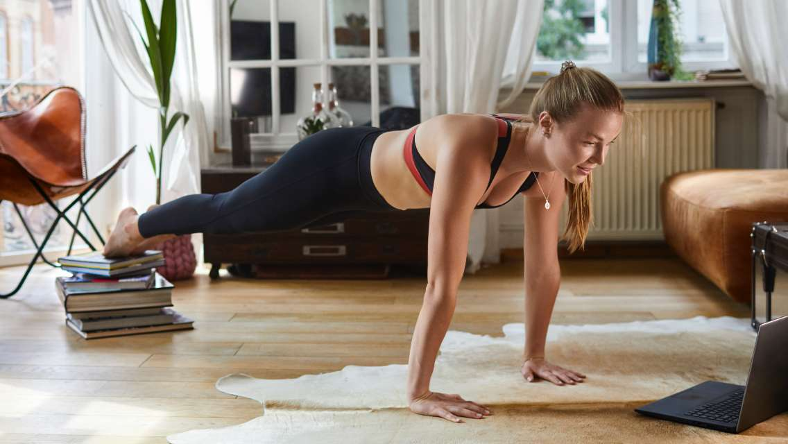 A woman doing a modified pushup at home.
